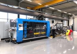KIEFEL Packaging hat eine 2100 m² große Produktionshalle auf Smart Hall Cooling umgestellt. Für eine deutlich verbesserte Raumluftqualität sorgt die gekühlte Frischluft, die zugfrei durch den grauen Schlauch oberhalb der Maschine eingeblasen wird.